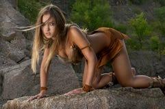 Donna primitiva che sta su una roccia Fotografie Stock Libere da Diritti