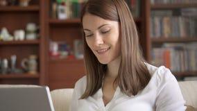 Donna professionale sorridente attraente che lavora al computer portatile a casa concetto dell'Di casa ufficio video d archivio