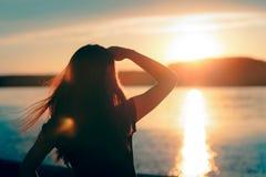 Donna promettente felice che esamina il tramonto dal mare immagini stock libere da diritti