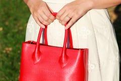 Donna recentemente impegnata che tiene borsa di cuoio rossa Immagine Stock