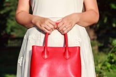 Donna recentemente impegnata che tiene borsa di cuoio rossa Fotografia Stock Libera da Diritti