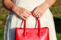 Donna recentemente impegnata che tiene borsa di cuoio rossa Fotografie Stock Libere da Diritti