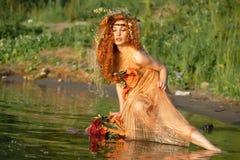 Donna Red-haired che si siede in acqua. Fotografie Stock Libere da Diritti