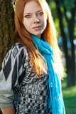 Donna Red-haired vicino all'albero Immagine Stock