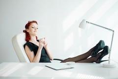 Donna Redheaded nel posto di lavoro Fotografia Stock Libera da Diritti