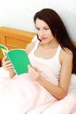 Donna Relaxed che legge un libro in base. Immagini Stock