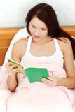 Donna Relaxed che legge un libro in base. Immagini Stock Libere da Diritti