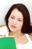 Donna Relaxed che legge un libro in base. Fotografia Stock Libera da Diritti