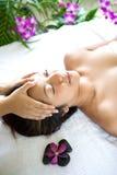 Donna restful mentre avendo un massaggio capo Immagine Stock