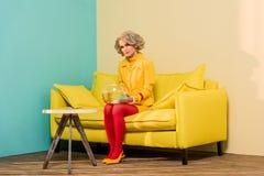 donna in retro abbigliamento luminoso con il pesce dorato in acquario sul sofà all'appartamento variopinto, bambola Fotografie Stock