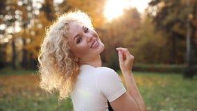 Donna riccia che cammina nel parco e che gode del sole archivi video