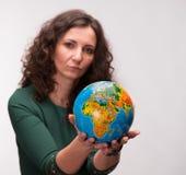 Donna riccia che tiene un globo Fotografie Stock