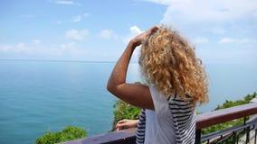 Donna riccia in occhiali da sole che considera mare da video d archivio