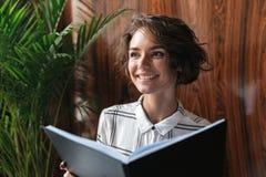Donna riccia sorridente con i documenti Fotografie Stock