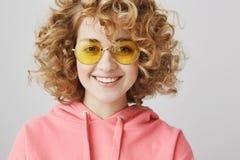 Donna riccio-dai capelli adorabile con gli occhiali da sole gialli alla moda che sorride alla macchina fotografica sopra fondo gr Immagine Stock