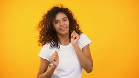Donna riccio-dai capelli allegra che balla attivamente, celebrando successo, buon umore, fortuna archivi video