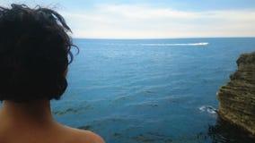 donna Riccio-dai capelli che sta sulla scogliera e che vede l'yacht del bianco sporco nel mare stock footage