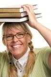 Donna ridente scioccamente sotto la pila di libri sulla testa Fotografia Stock