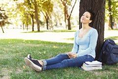 Donna rilassata che ascolta la musica su erba all'aperto Fotografie Stock Libere da Diritti