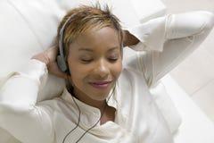 Donna rilassata che ascolta la musica sul riproduttore di CD portatile fotografia stock