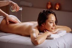Donna rilassata che ha massaggio con olio in stazione termale immagini stock