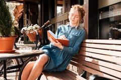 Donna rilassata che si siede sul banco e che scrive in taccuino fotografia stock