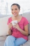 Donna rilassata che si siede sulla tazza della tenuta del sofà di caffè Immagini Stock Libere da Diritti