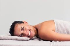 Donna rilassata che si trova sulla chaise-lounge di massaggio fotografia stock libera da diritti