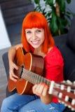 Donna rilassata del redhaid che gioca chitarra Fotografie Stock Libere da Diritti