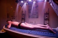 Donna rilassata di menzogne durante il trattamento della stazione termale. Terapia di colore. Fotografia Stock Libera da Diritti