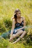 Donna rilassata di modo che si siede nel campo soleggiato Immagini Stock Libere da Diritti