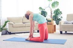 Donna rilassata graziosa che fa posizione di yoga del cammello Fotografia Stock