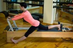 Donna risoluta che esegue allungando esercizio sul riformatore Fotografie Stock