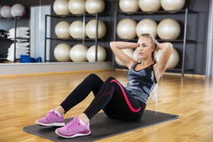 Donna risoluta che esegue gli scricchiolii sull'esercizio Mat In Gym Immagini Stock Libere da Diritti