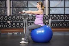 Donna risoluta che si esercita sulla palla di forma fisica Immagini Stock