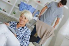 Donna rivestente di ferro degli anziani della lavanderia del badante maschio fotografia stock libera da diritti