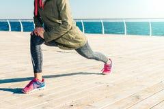 Donna in rivestimento, cappuccio e scarpe da tennis facenti allungamento sulla spiaggia Fotografia Stock