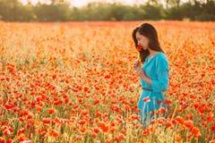Donna romantica che odora un papavero rosso nel campo fotografie stock libere da diritti