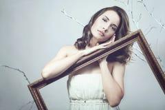 Donna romantica che tiene una cornice sul fondo dell'albero Fotografia Stock Libera da Diritti