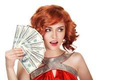 Donna rossa dei capelli che giudica i dollari disponibili Fotografia Stock Libera da Diritti