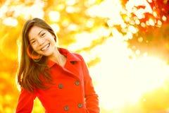 Donna rossa del cappotto di trincea di autunno nel fogliame del chiarore del sole immagini stock
