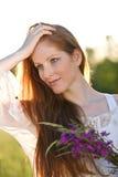 Donna rossa lunga dei capelli con il mazzo del fiore Immagine Stock