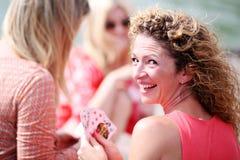 Donna rossa riccia dei capelli che ride mentre carte da gioco con gli amici Immagini Stock