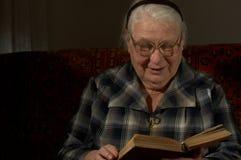 Donna saggia dietro la lettura dal libro fotografie stock