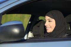 Donna saudita araba felice che conduce un'automobile immagine stock