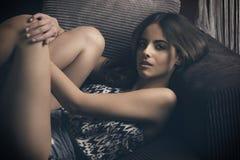 Donna sbalorditiva rilassata sul sofà fotografie stock libere da diritti