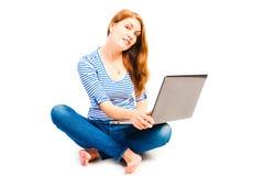 Donna scalza che si siede con un computer portatile Fotografia Stock Libera da Diritti