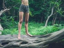 Donna scalza dei giovani che sta sull'albero caduto in foresta Immagini Stock Libere da Diritti