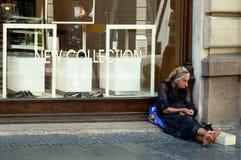 Donna scalza senza tetto che si siede sulla pavimentazione davanti al negozio di scarpe fotografie stock libere da diritti