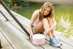 Donna in scarpe da tennis che aprono il contenitore di regalo Fotografie Stock Libere da Diritti